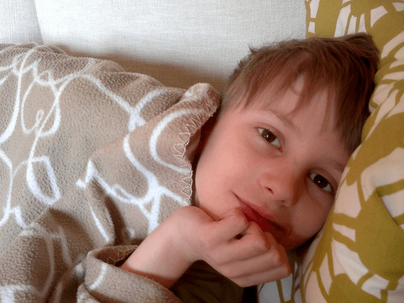 A smiling kid, wide awake on bed