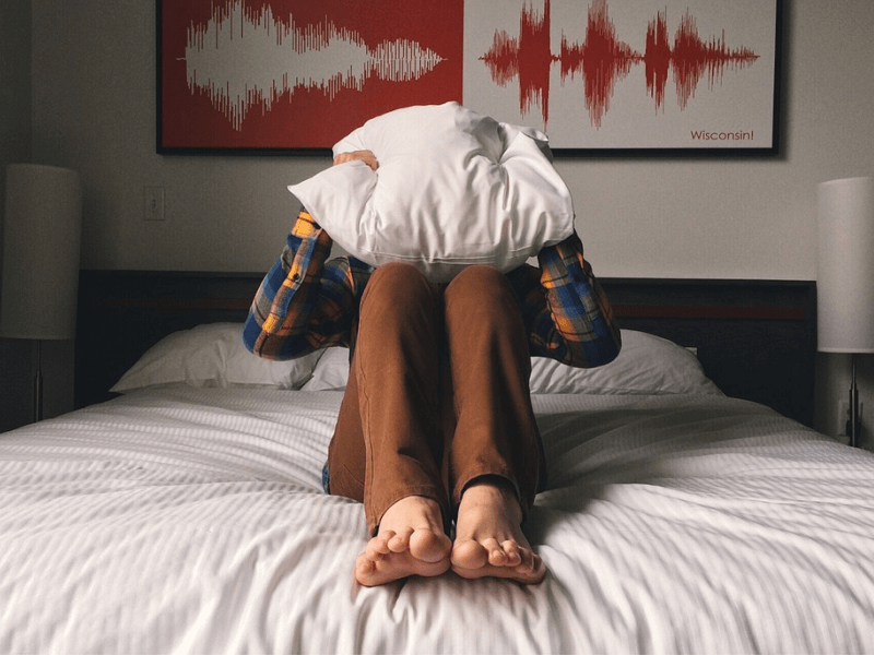 A person on a bed covering their face with a pillow