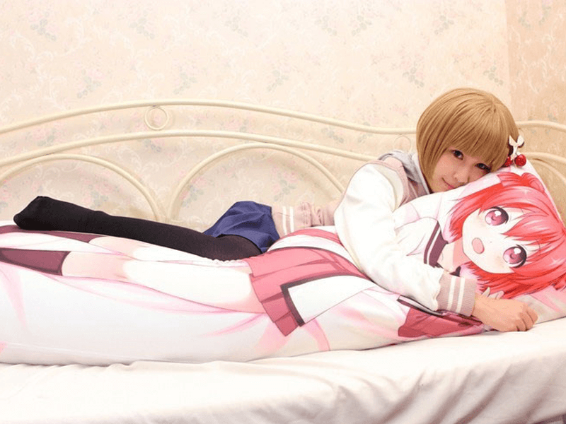 girl in schoolgirl uniform on bed hugging anime dakimakura pillow