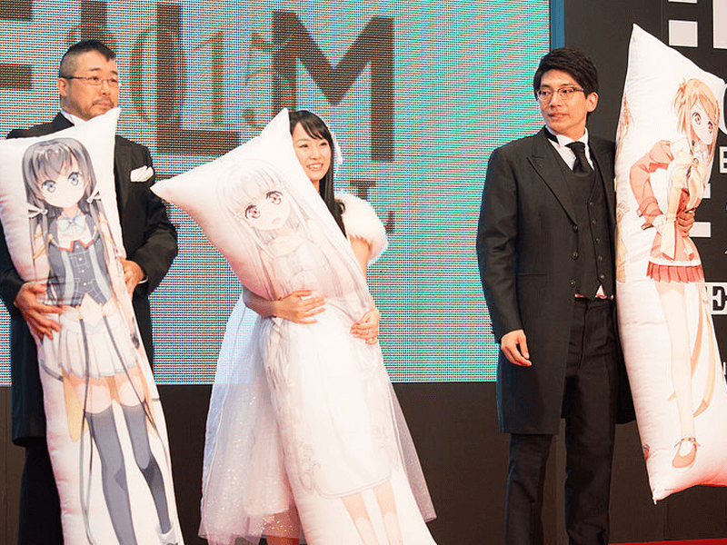 two men and one woman on stage and wearing formal clothes while holding anime dakimakura pillows