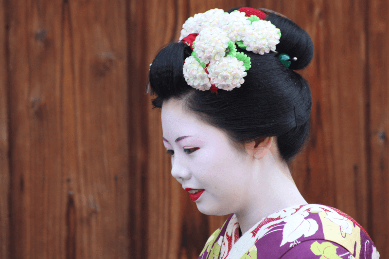 profile portrait of geisha apprentice with traditional shimada hairstyle and flowers in her hair