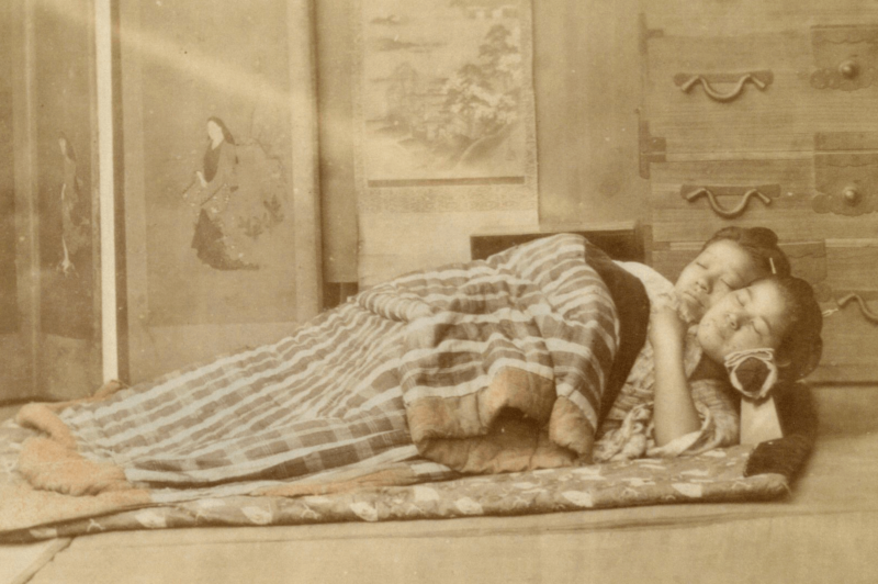 old photo of two geisha sleeping on the floor with blankets and takamakura