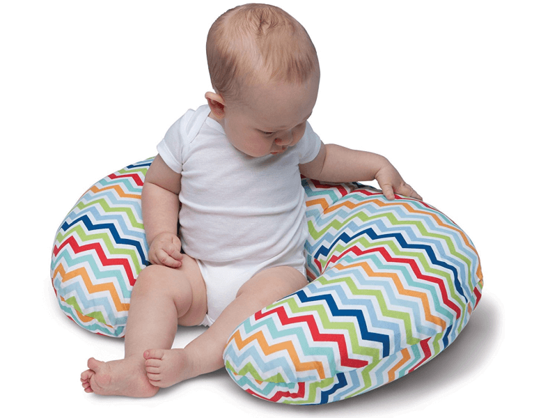 baby sitting on inside curve of u-shaped pillow