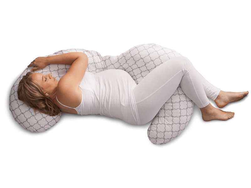 pregnant woman using curved orthopedic pillow while in side sleeping position