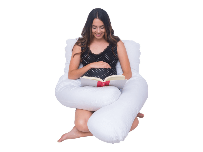 pregnant woman using full length u-shaped body pillow while sitting up and reading
