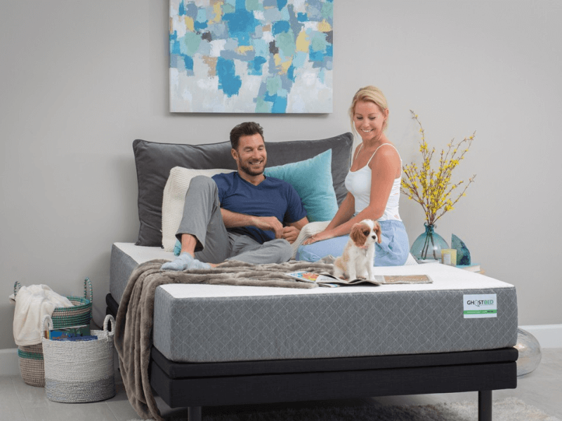 man, woman and dog sitting on GhostBed mattress with pillows and blanket