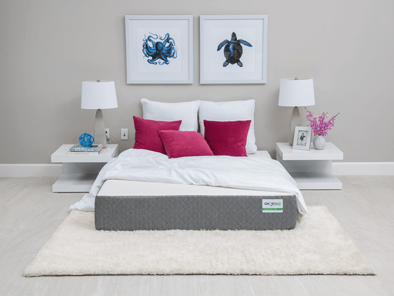 GhostBed mattress set up on floor with white run underneath and pillows and blanket on top