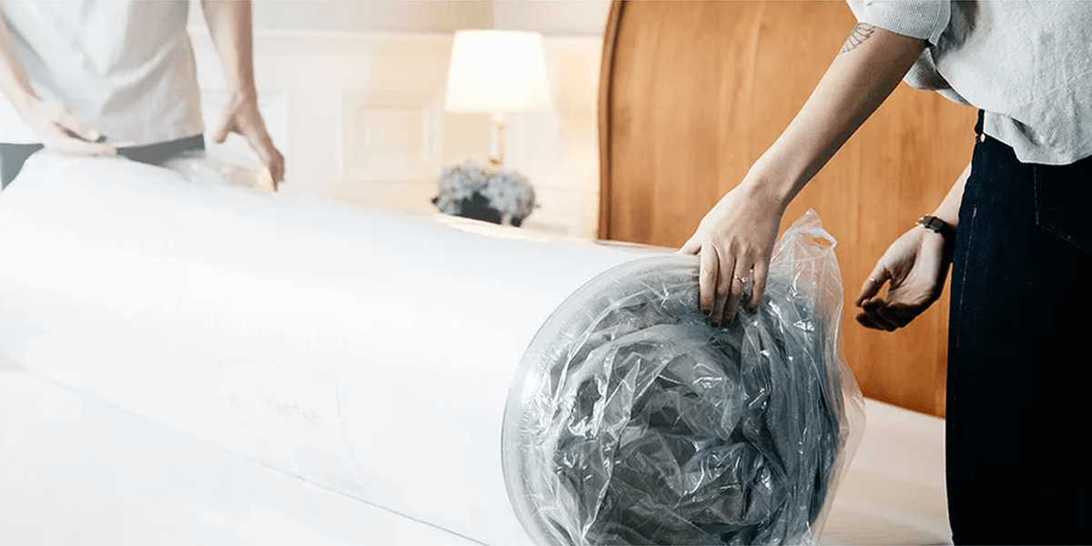 Nectar mattress being unpacked and unrolled onto a bed frame by two people
