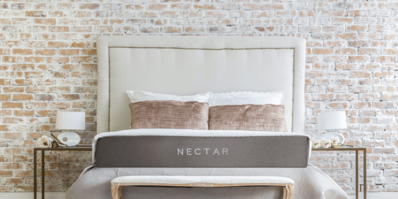 Nectar mattress set up with two bedside table against a brick wall