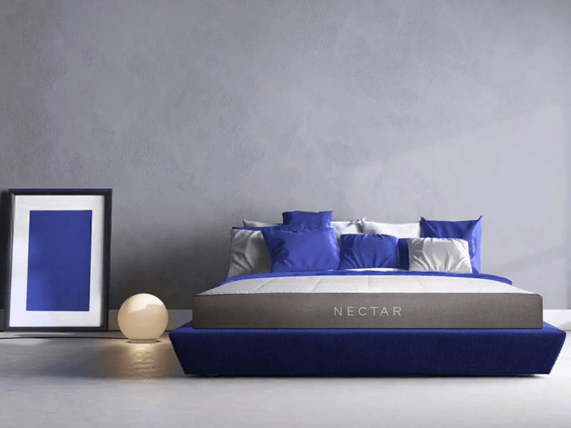 Nectar mattress with blue and gray pillows and blue foundation, on gray background