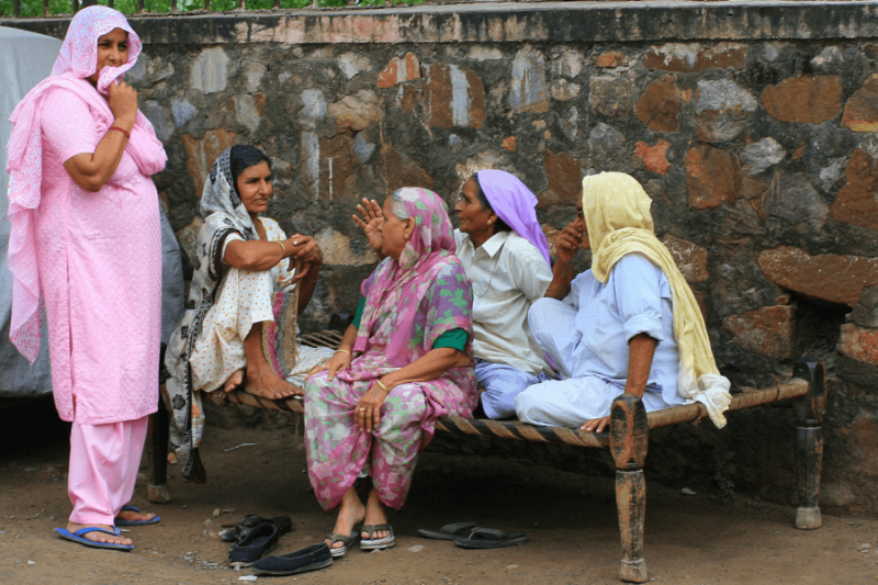 four women sitting on charpai and talking while a fifth woman stands and listens