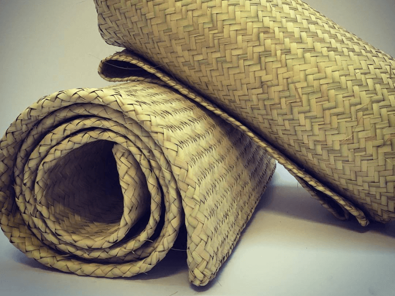 Two rolled up handwoven petate mats