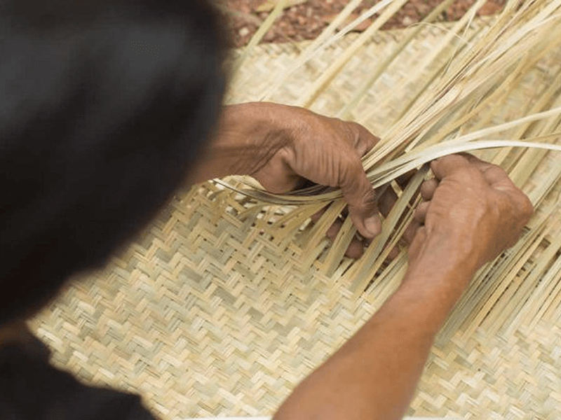Hands weaving a straw mat