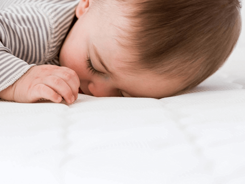 Baby lying face down on Newton Wovenaire crib mattress