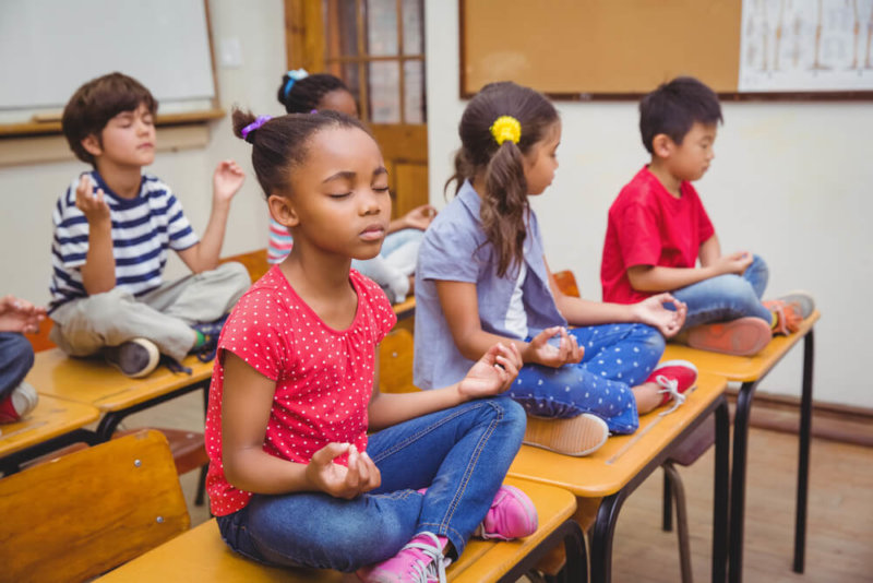 meditating children sitting in lotus position on top of school desks