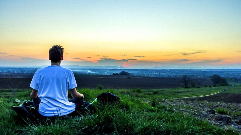 back view of man in lotus position on grass near ocean