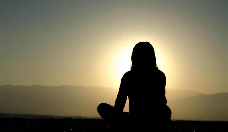 silhouette of long haired person sitting and looking at mountain view