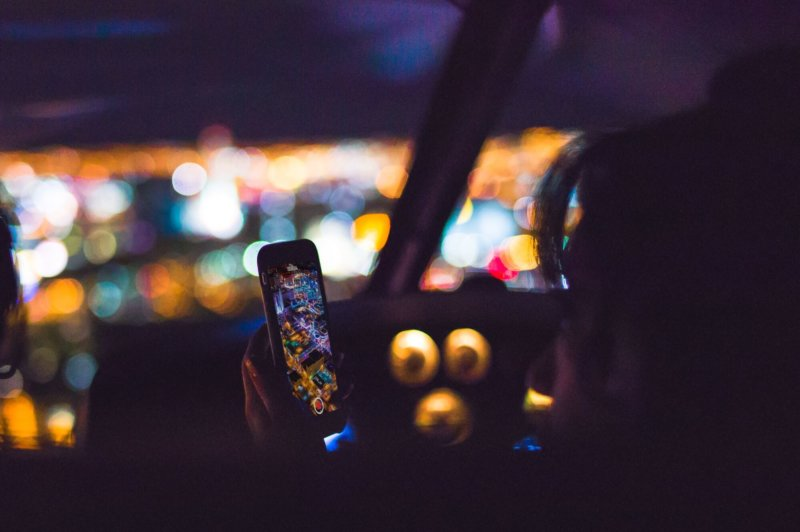 Person using smartphone in the dark with city lights in the background