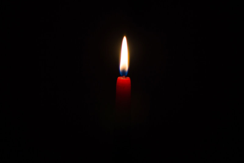 Lone candlelight in darkness