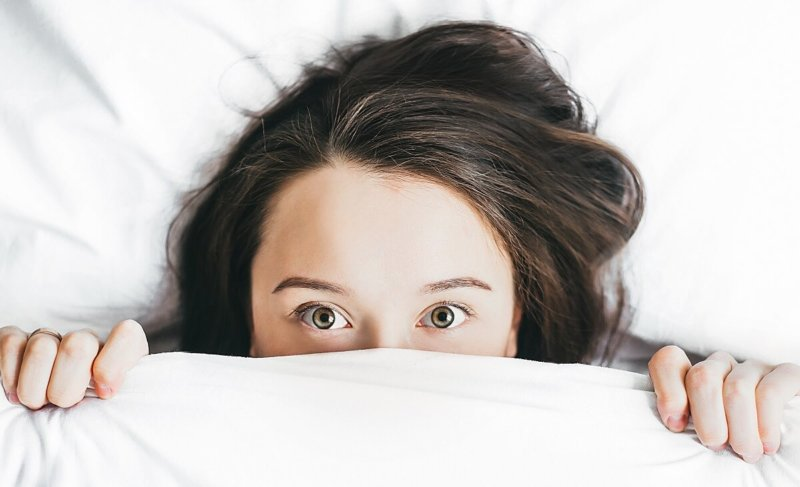 Woman lying under the covers with eyes open