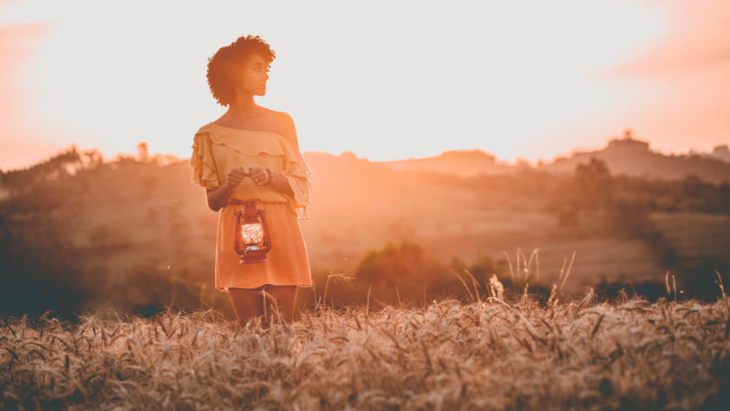 Woman carrying lamp in open field during sunset