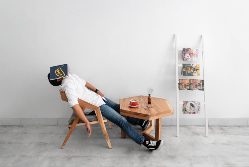 man slumped on a chair, asleep with book over face