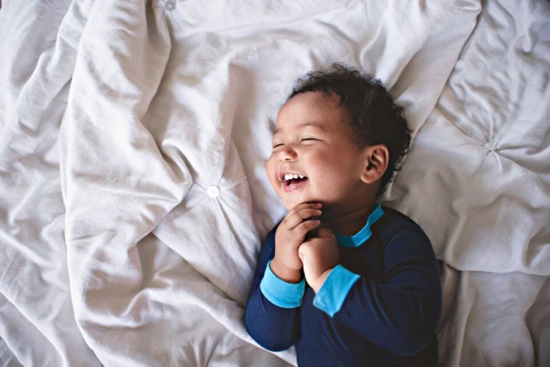 child happy in bed