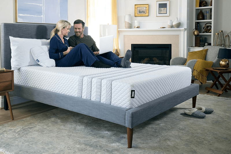 Leesa Sapira mattress with couple wearing pajamas sitting on top