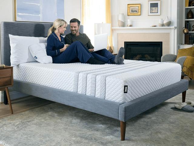 Leesa Sapira mattress with couple wearing pajamas sitting on top