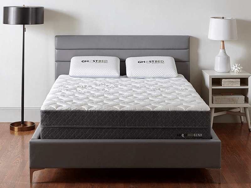 front view of GhostBed Luxe mattress on bedframe between floor lamp and bedside table with lamp