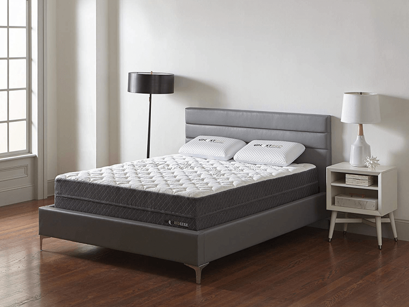 three fourths view of GhostBed Luxe mattress on bedframe between floor lamp and bedside table with lamp