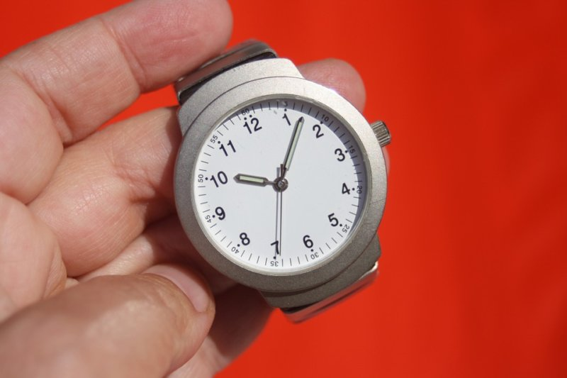 hand holding wristwatch on red background