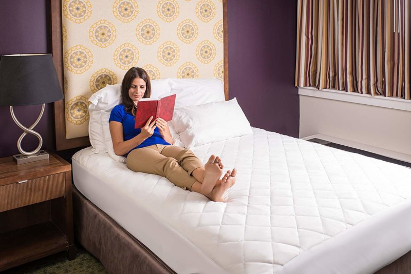 woman reading on bed fitted with Hanna Kay mattress pad