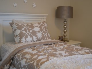 Bed next to nightstand with bedside lamp