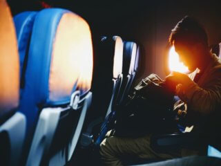 Person looking through their bag while sitting on the window seat of a plane